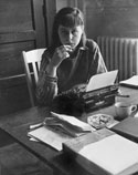 Carson McCullers sitting at a desk with a typewriter